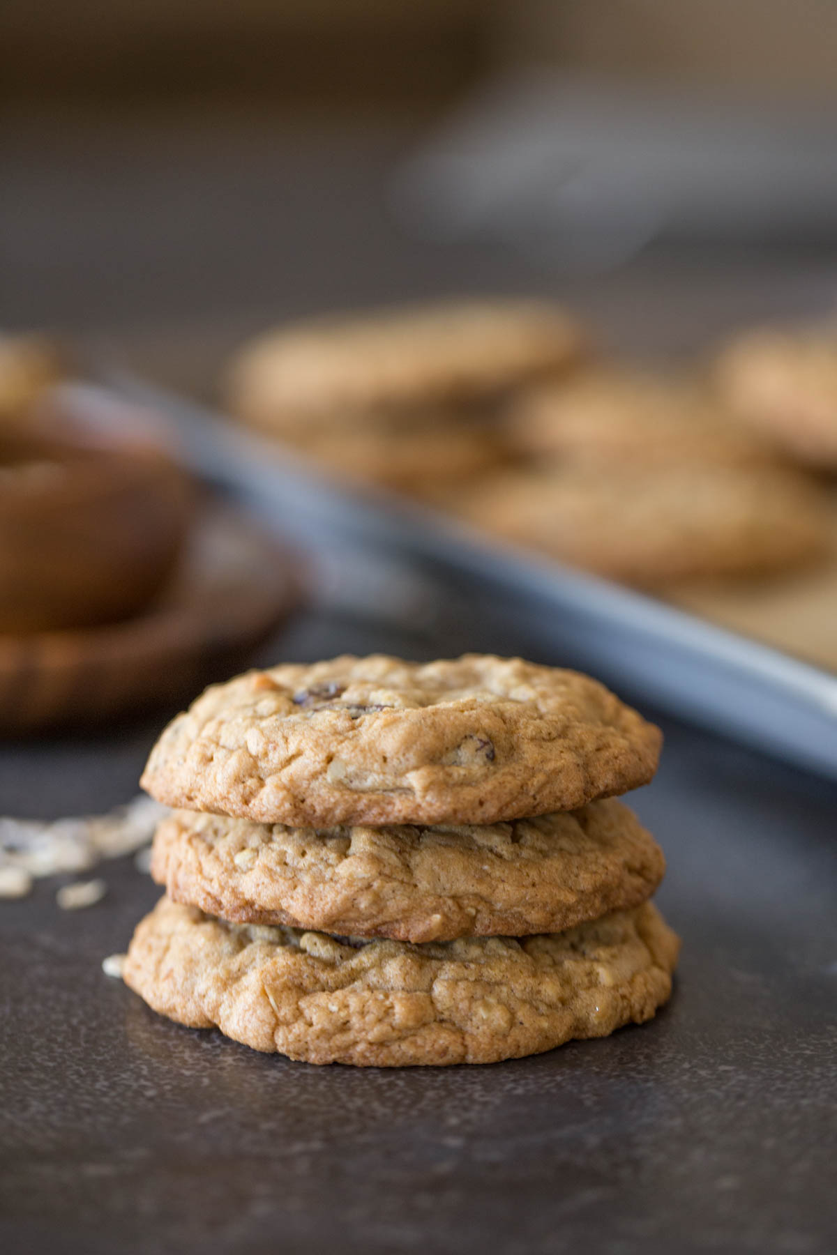 Three Bakery Style Oatmeal Raisin Cookies stacked on top of each other.