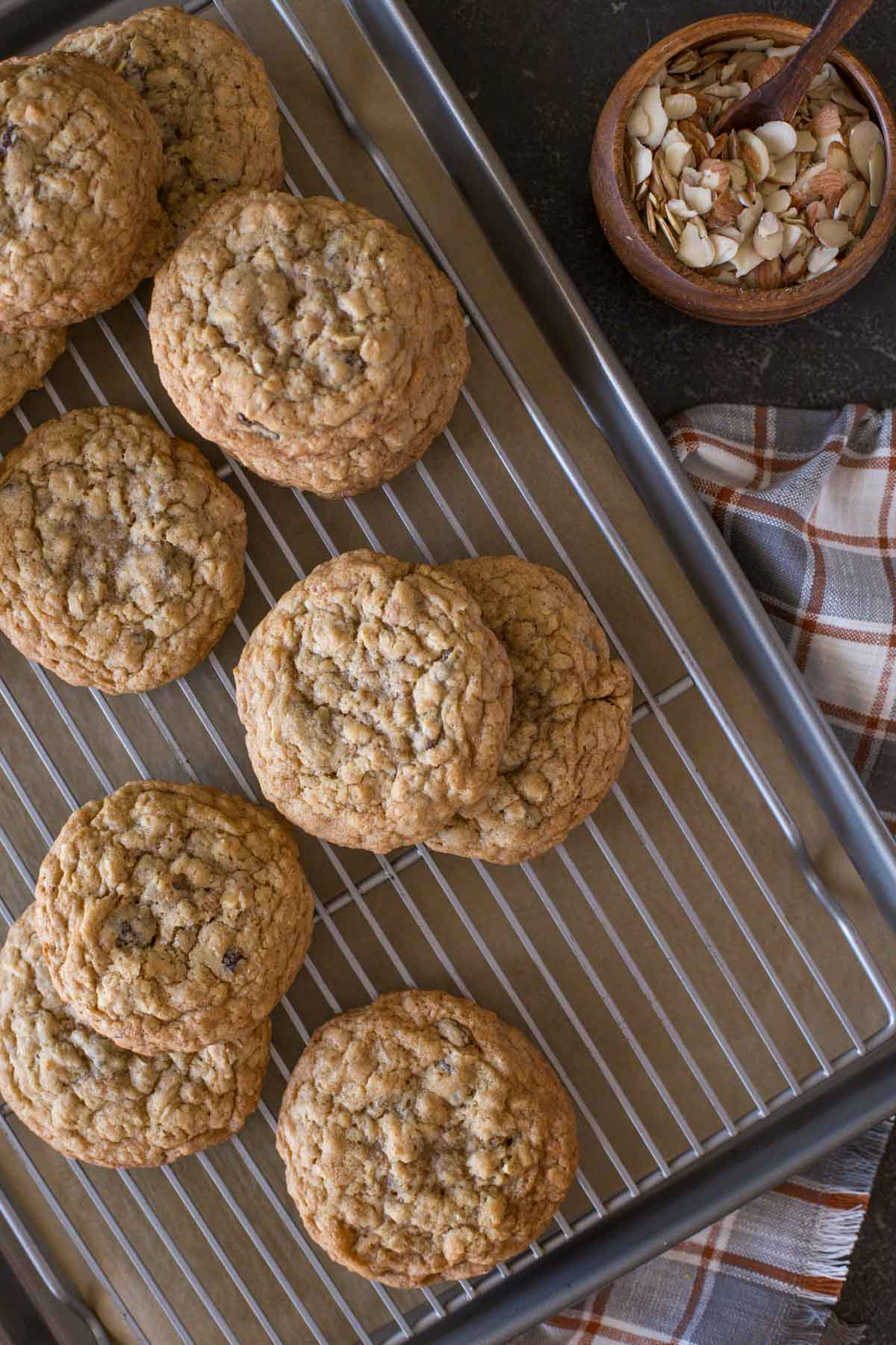 Bakery Style Oatmeal Raisin Cookies on a cooling rack that is on top of a parchment paper lined baking sheet, with a small wood bowl of slice almonds next to it.