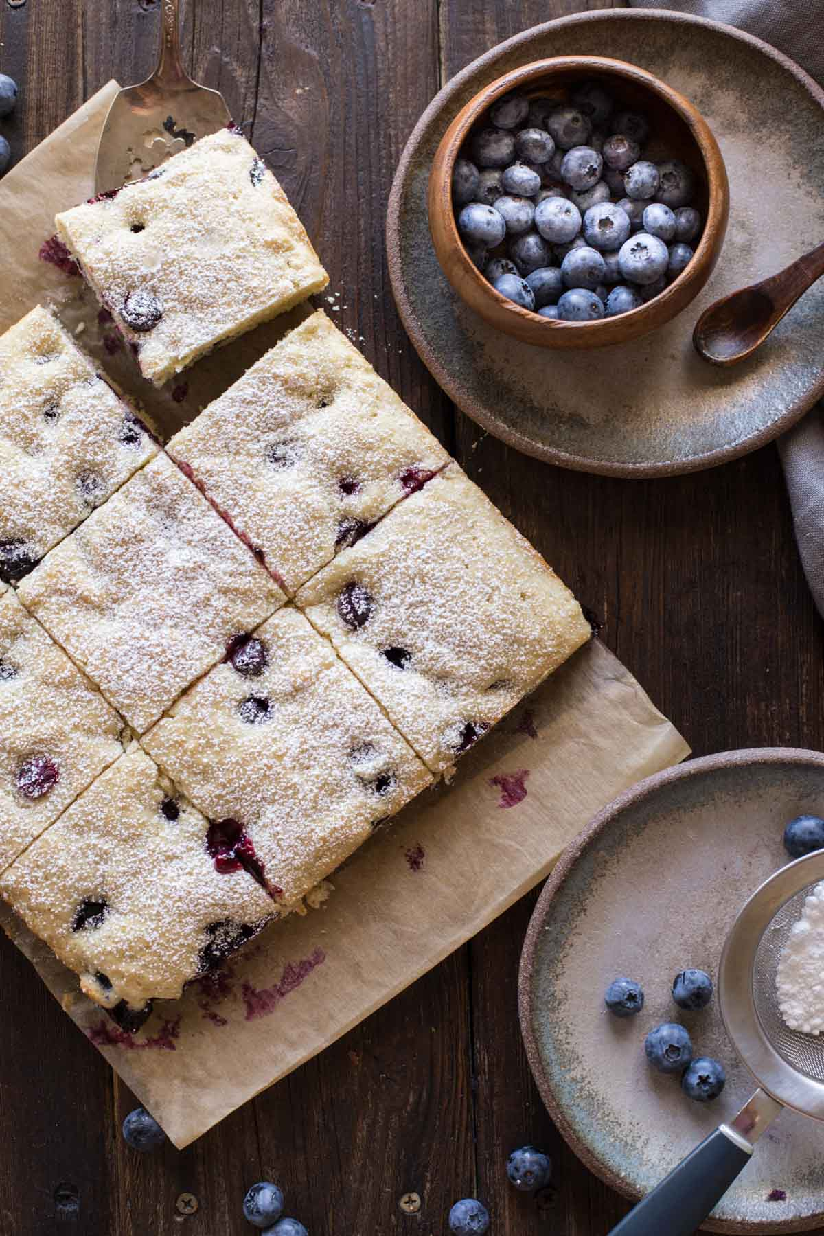 Buttermilk Blueberry Snack Cake sliced on a piece of parchment paper, with a small wood bowl of blueberries on a plate next to it, as well as a plate with a sifter full of powdered sugar.