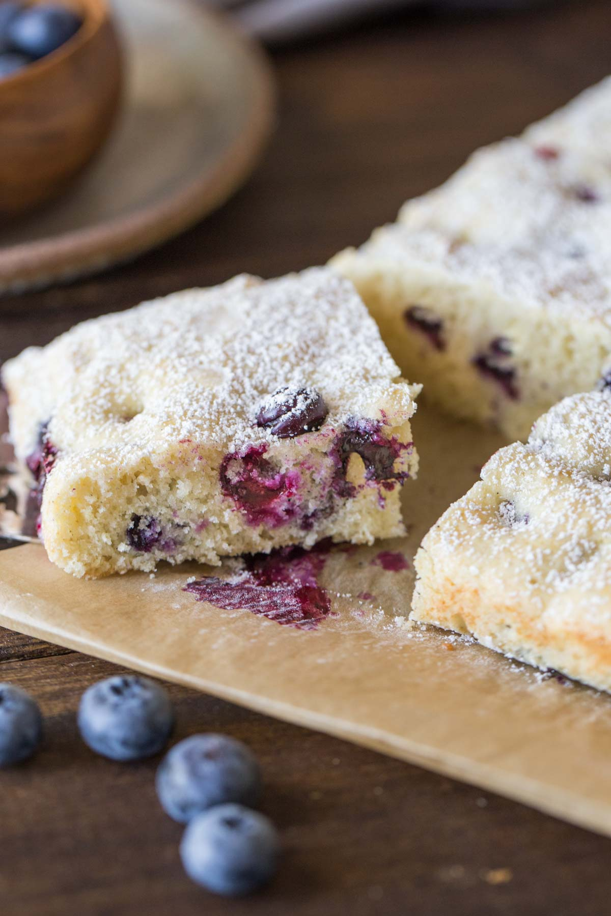 Buttermilk Blueberry Snack Cake sliced on a piece of parchment paper.