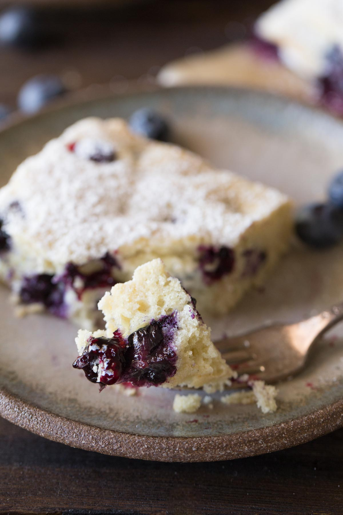 A piece of Buttermilk Blueberry Snack Cake on a plate, with a fork with a bite of cake on it.