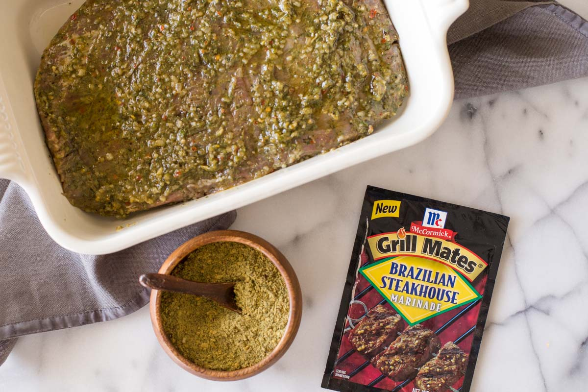 Flank steak in a baking dish, covered with the marinade, with a packet of the McCormick Brazilian Steakhouse Marinade next to the dish, as well as a small wood bowl of the spices with a wooden spoon in it.