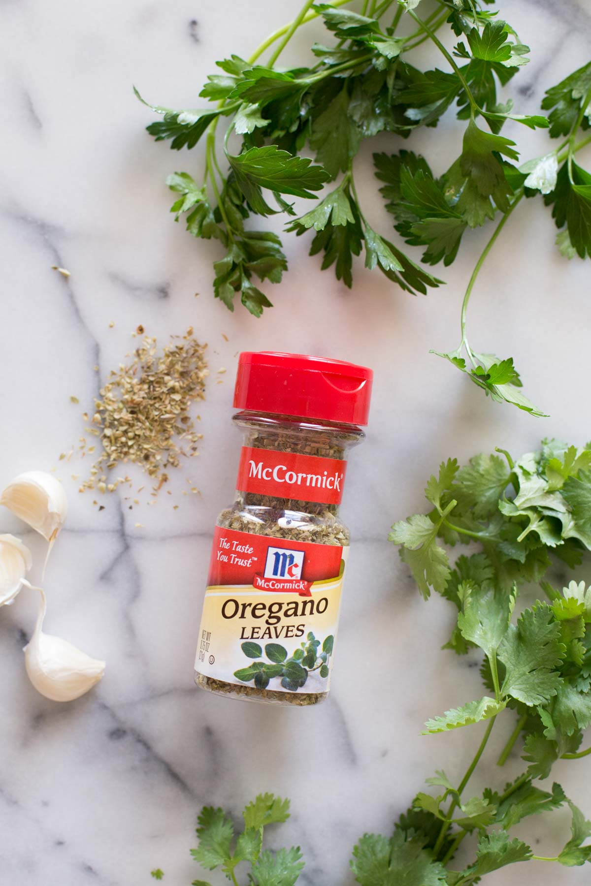 A spice container of McCormick Oregano Leaves, fresh parsley, cilantro, and garlic for the chimichurri.