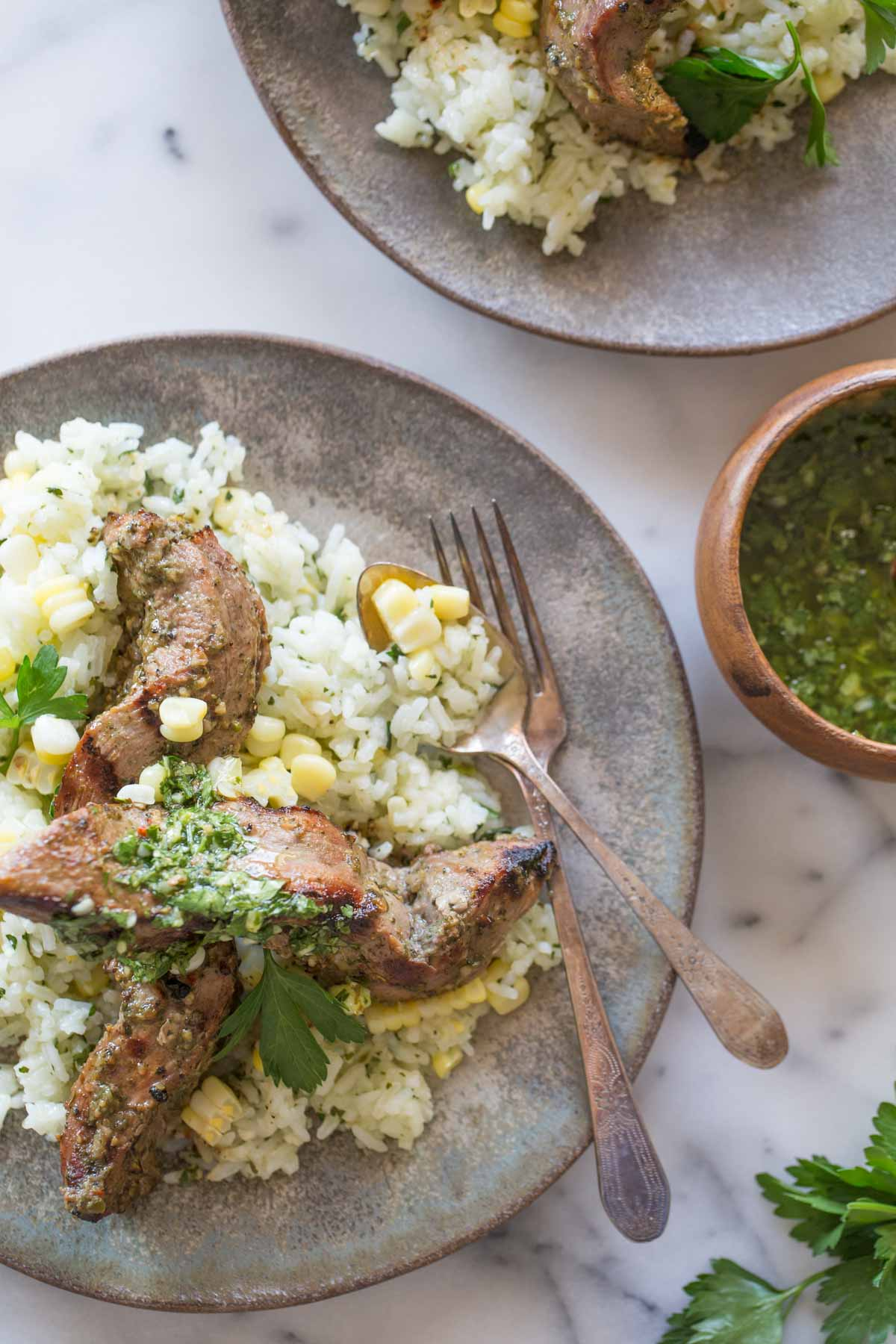 Brazilian Grilled Flank Steak resting on a bed of Chimichurri Rice, on a plate with a fork and a spoon, with another plate of Brazilian Grilled Flank Steak resting on a bed of Chimichurri Rice next to it, as well as a small bowl of chimichurri.