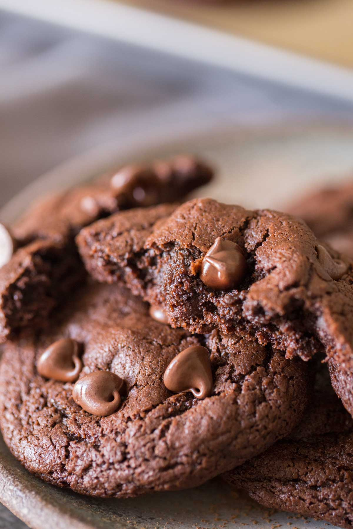 A plate of One Bowl Triple Chocolate Brownie Cookies, with one of the cookies broken in half.