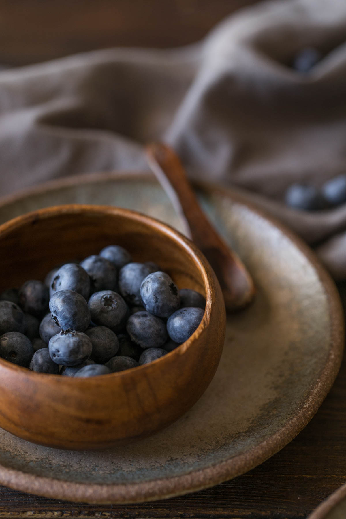 A small wood bowl of blueberries sitting on a plate with a small wooden spoon.