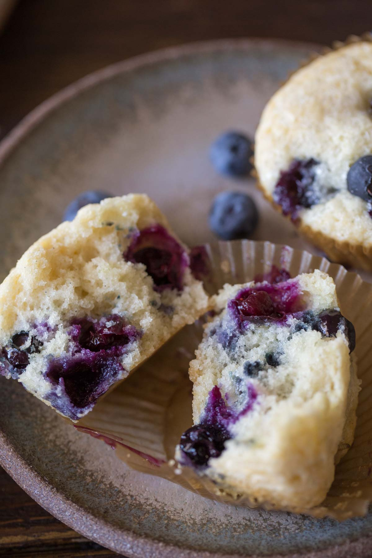 A Vanilla Blueberry Buttermilk Muffin split in half, sitting on a plate with another whole muffin and some blueberries.