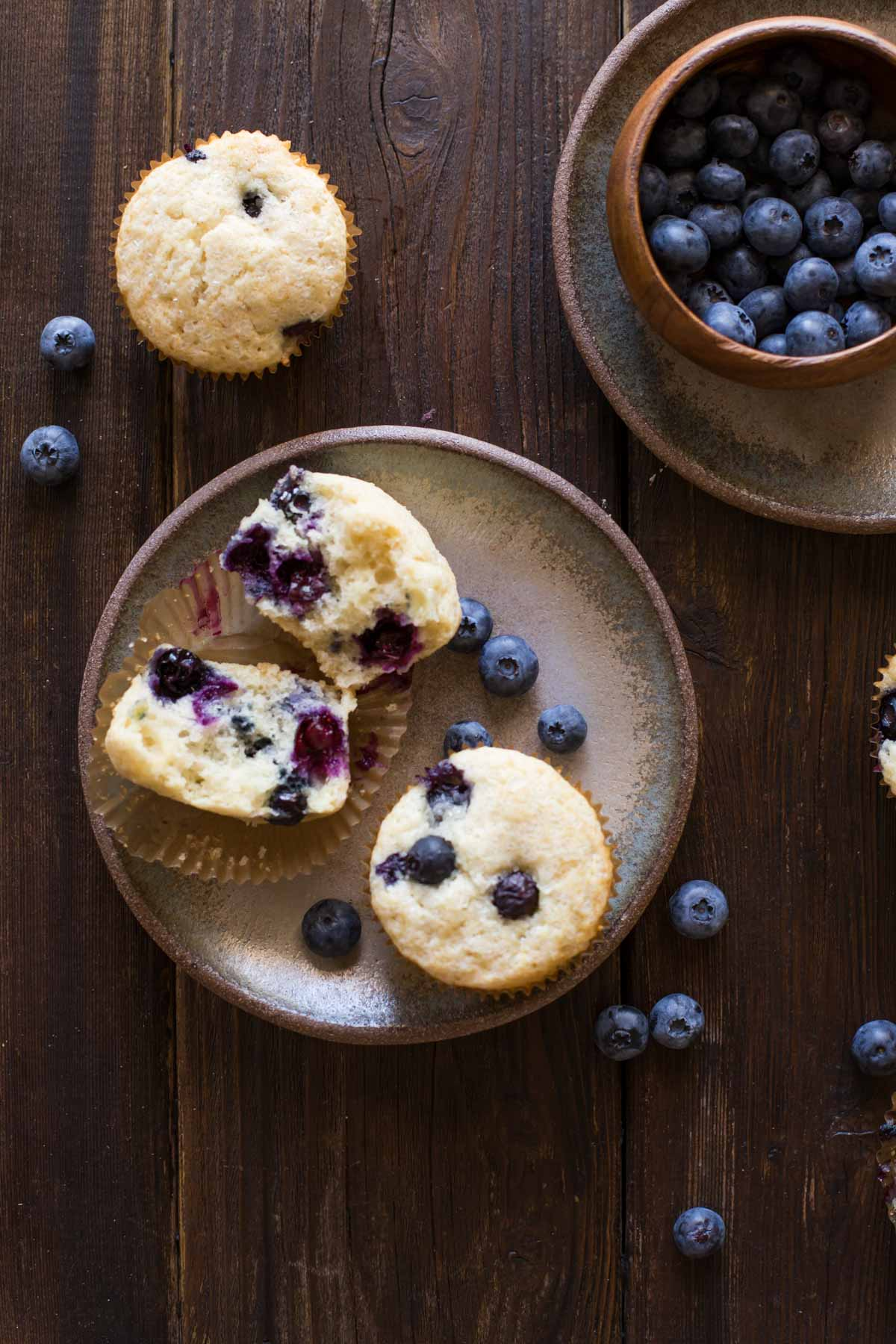 A Vanilla Blueberry Buttermilk Muffin split in half, sitting on a plate with a whole muffin and some blueberries, with a muffin and blueberries near the plate, and a wood bowl of blueberries sitting on another plate.