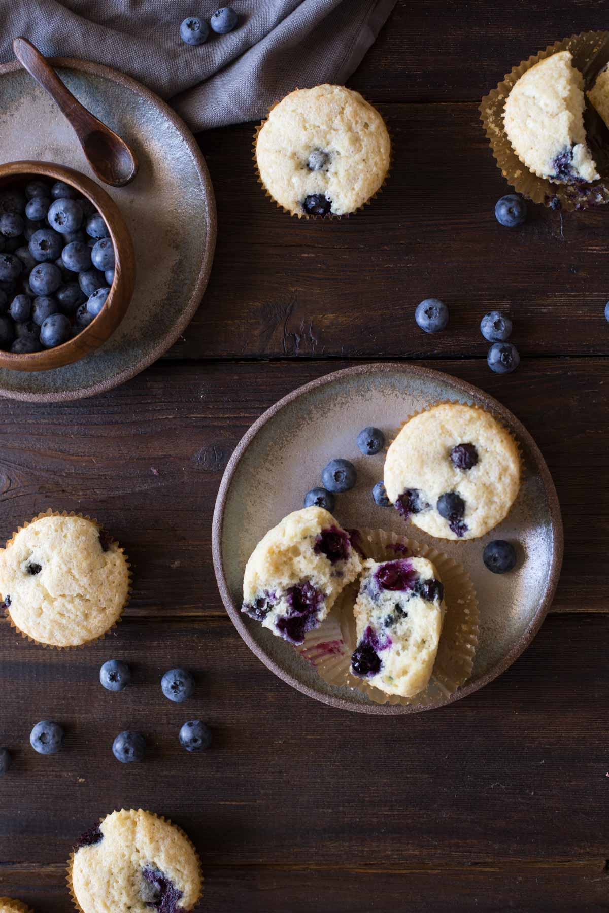 A Vanilla Blueberry Buttermilk Muffin split in half, sitting on a plate with a whole muffin and some blueberries, with more muffins and blueberries near the plate, and a wood bowl of blueberries sitting on another plate.