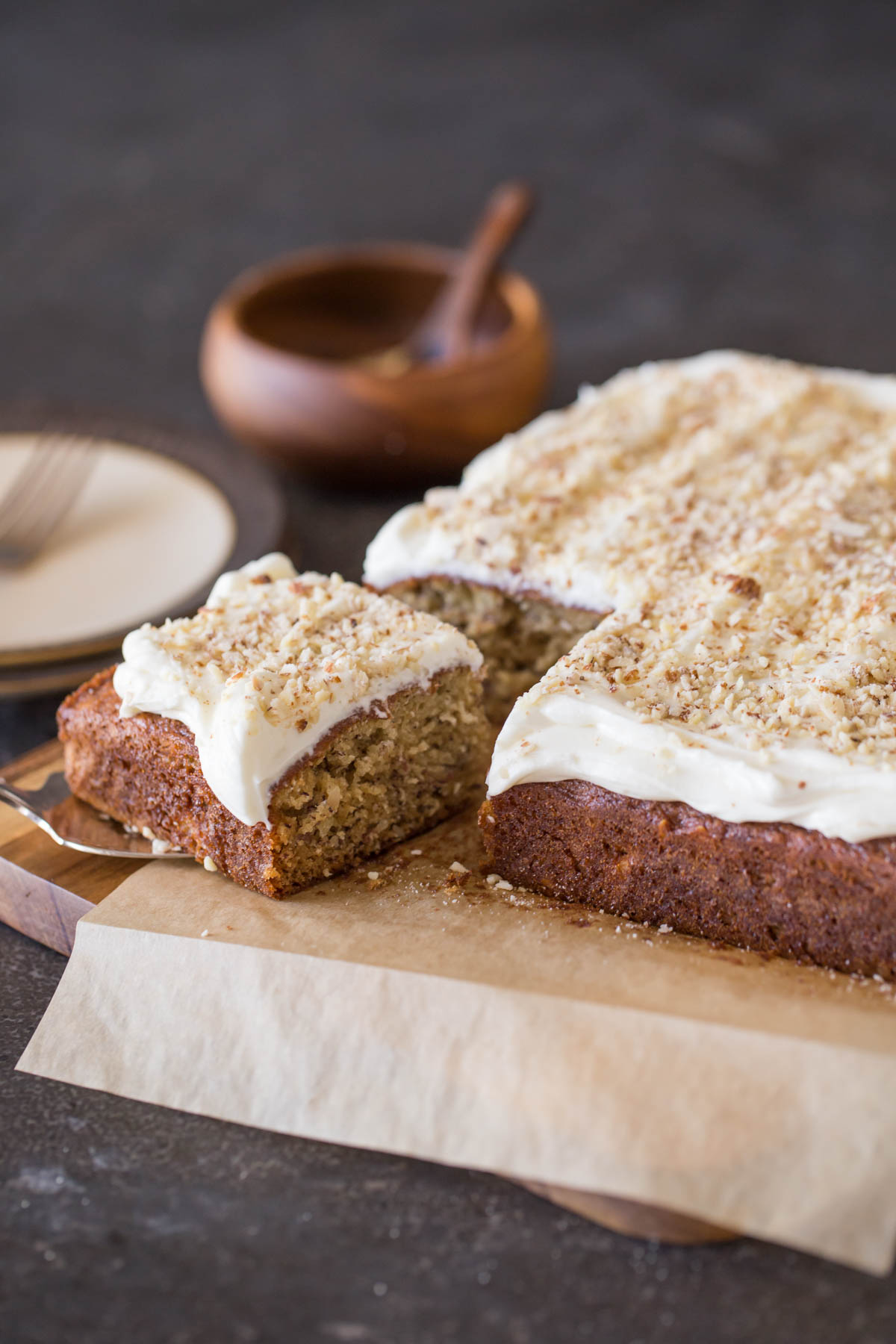 Banana Cake with Fluffy Cream Cheese Frosting on parchment paper on top of a cutting board, with the corner piece on top of a serving spatula.
