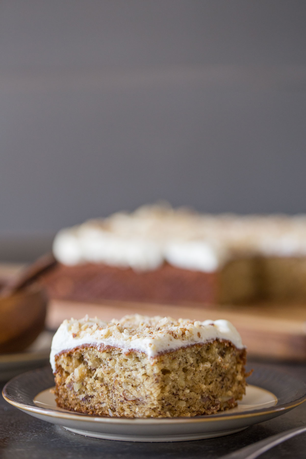 A piece of Banana Cake with Fluffy Cream Cheese Frosting on a plate, with the rest of the cake in the background.