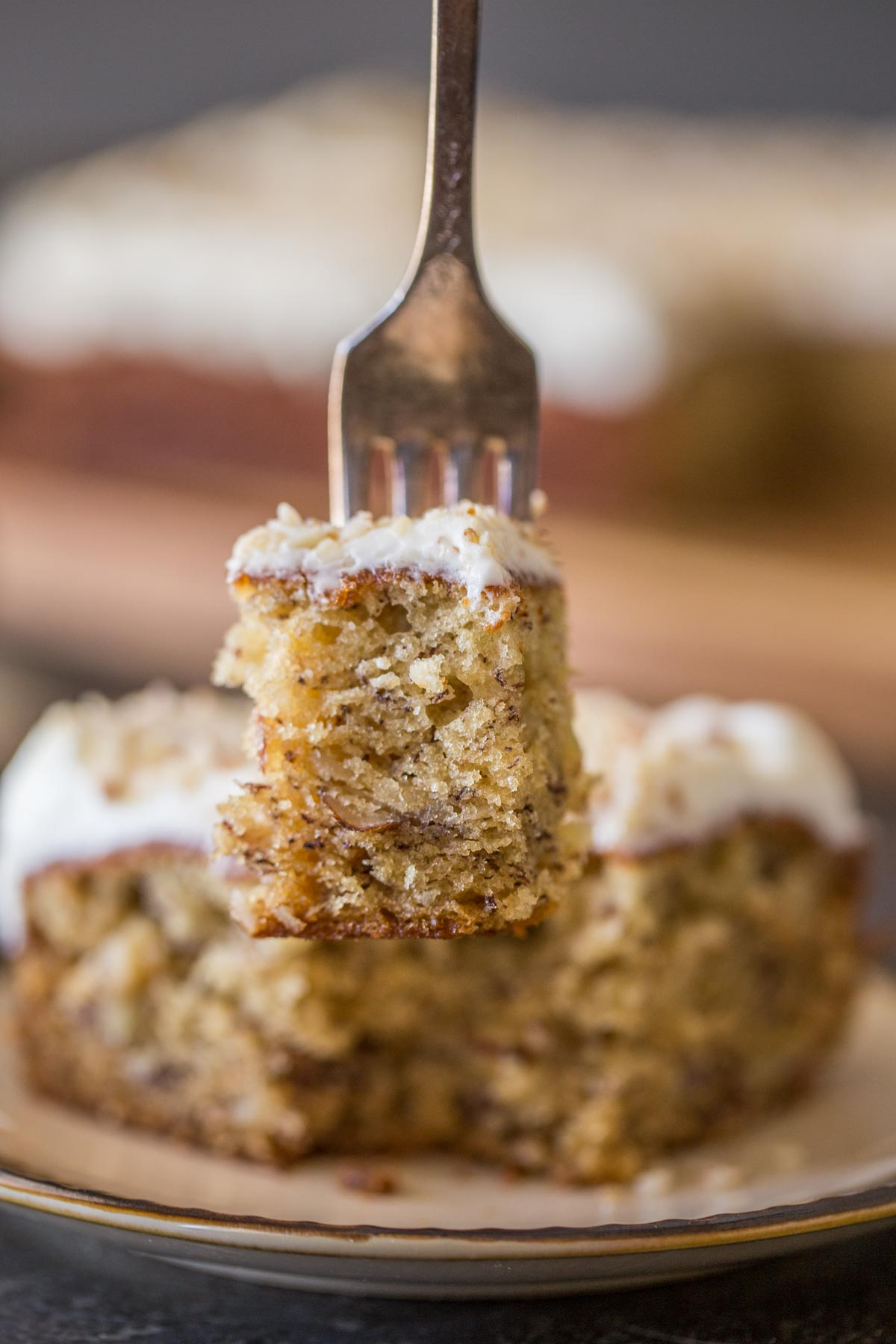 A fork with a bite of the Banana Cake with Fluffy Cream Cheese Frosting on it, with the rest of the piece of cake on a plate in the background.