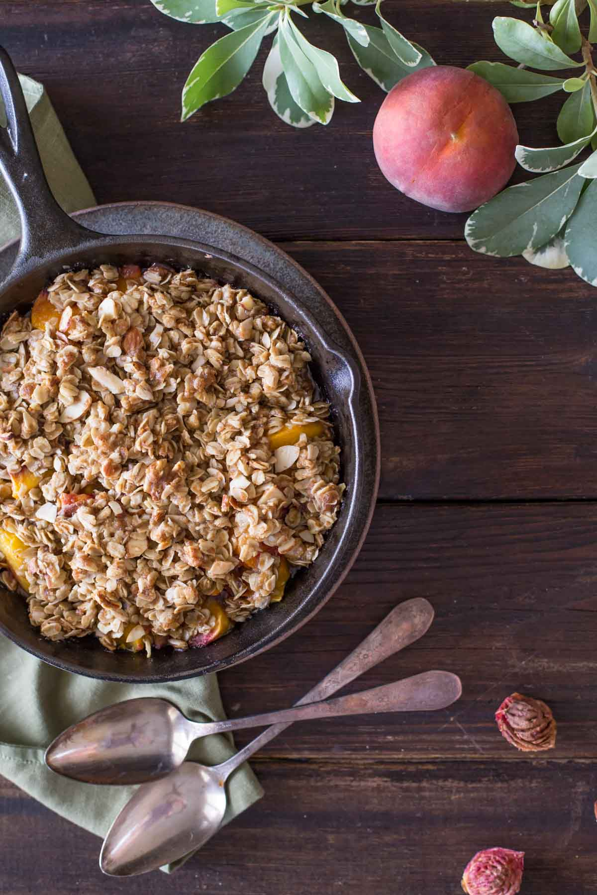 Easy Skillet Peach Crisp, with two spoons next to the skillet, as well as a whole peach and a couple peach pits.