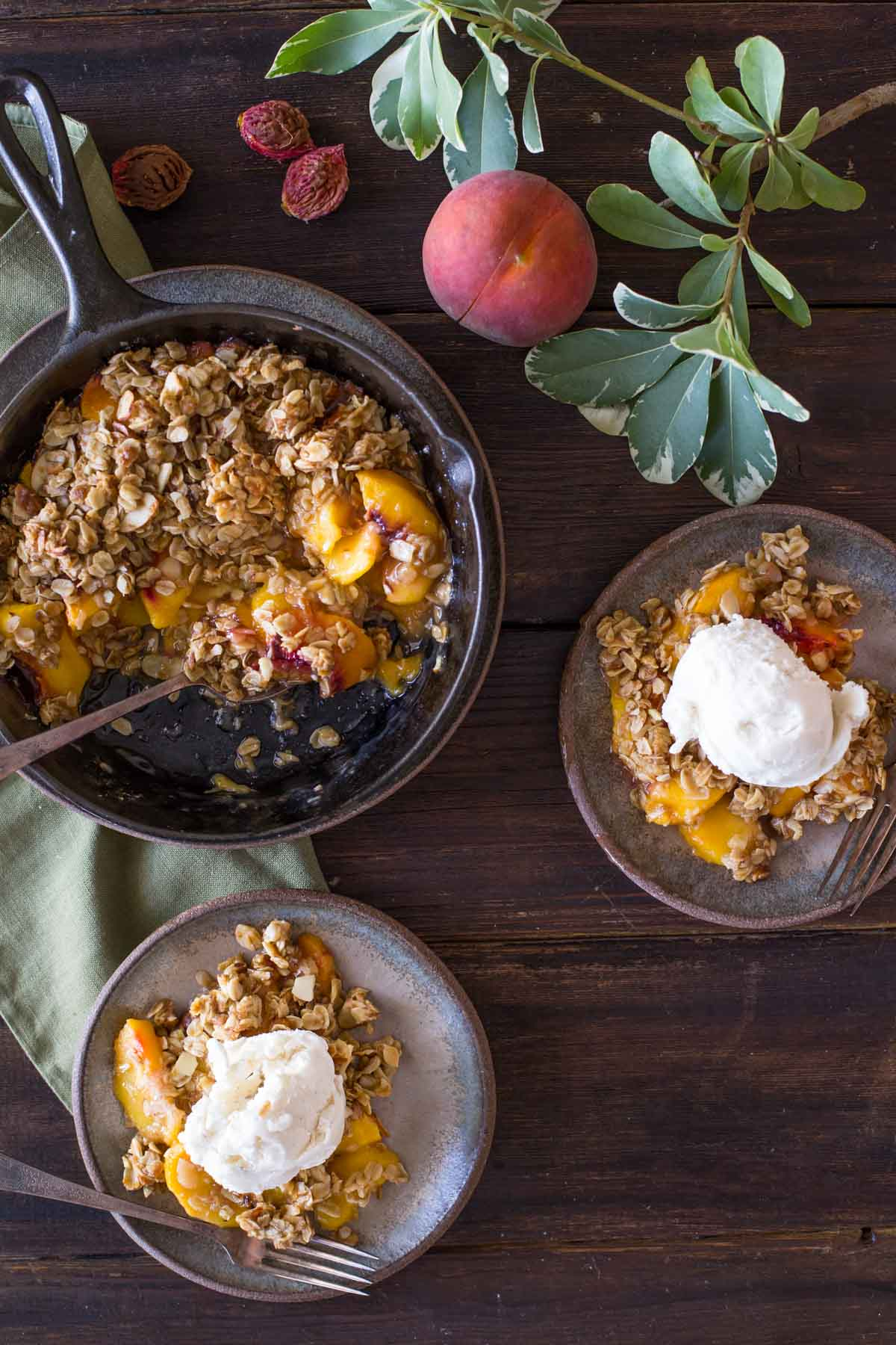 Two plates of Easy Skillet Peach Crisp topped with vanilla ice cream, sitting next to the skillet of Peach Crisp, as well as a whole peach and a few peach pits.