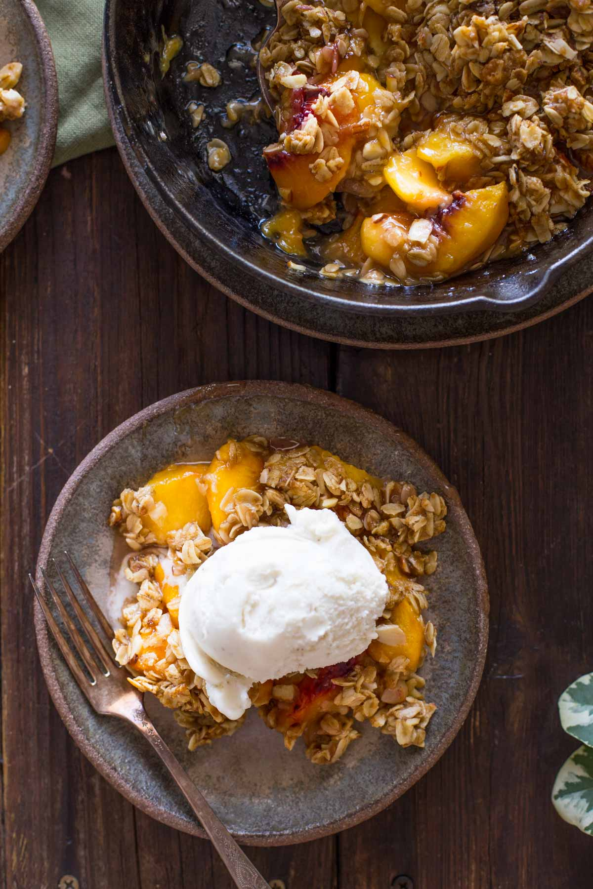 A plate of Easy Skillet Peach Crisp topped with vanilla ice cream, sitting next to the skillet of Peach Crisp.