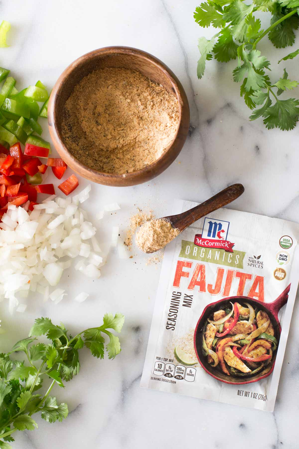A packet of McCormick Organics Fajita Seasoning Mix, with a small wood spoon of the seasoning mix next to a small wood bowl of the seasoning mix, along with copped green and red peppers, chopped onions and fresh cilantro.