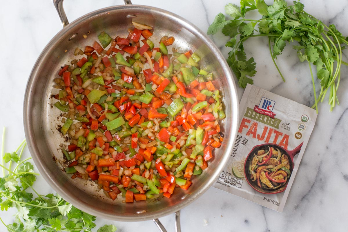 A skillet with the cooked red and green peppers and onions in it, with a packet of the McCormick Organics Fajita Seasoning Mix next to it.