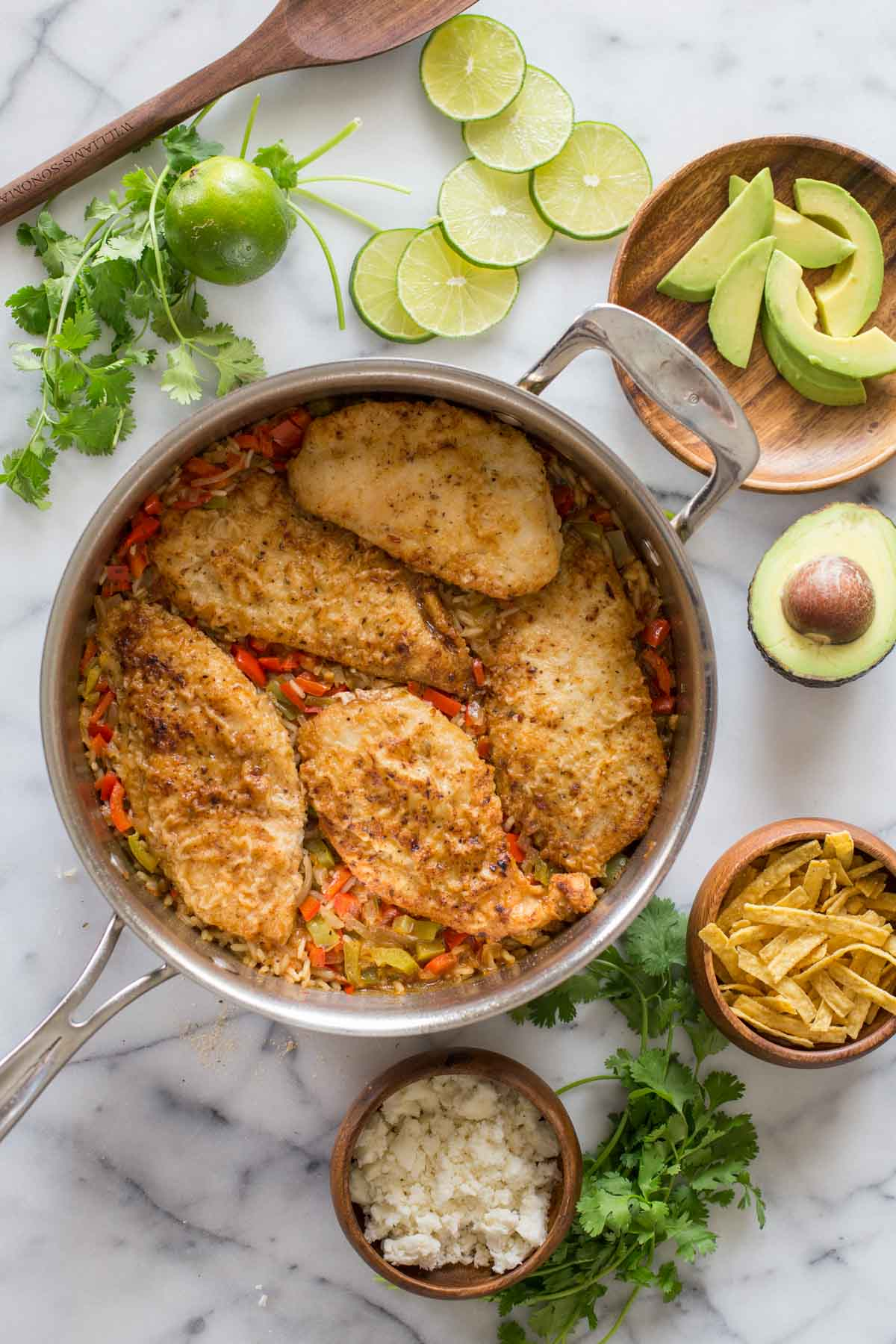 One Skillet Fajita Style Chicken and Rice, with a little bowl of crumbled queso fresco, fresh cilantro, a small bowl of tortilla strips, a half of an avocado, a plate of sliced avocado, some slices of lime, and a whole lime next to the skillet.