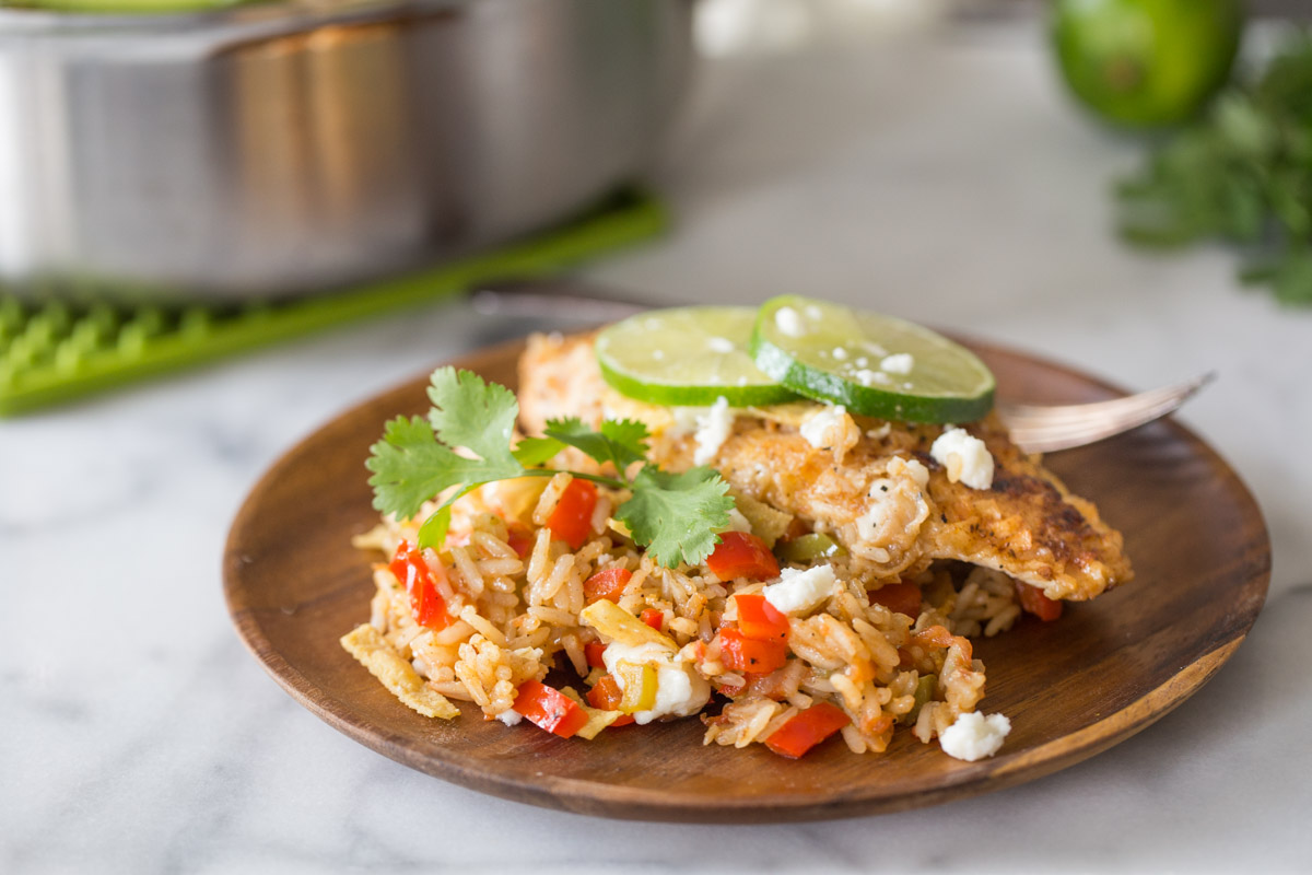 A plate with a serving of One Skillet Fajita Style Chicken and Rice, topped with crumbled queso fresco, fresh cilantro, tortilla strips, and lime slices.