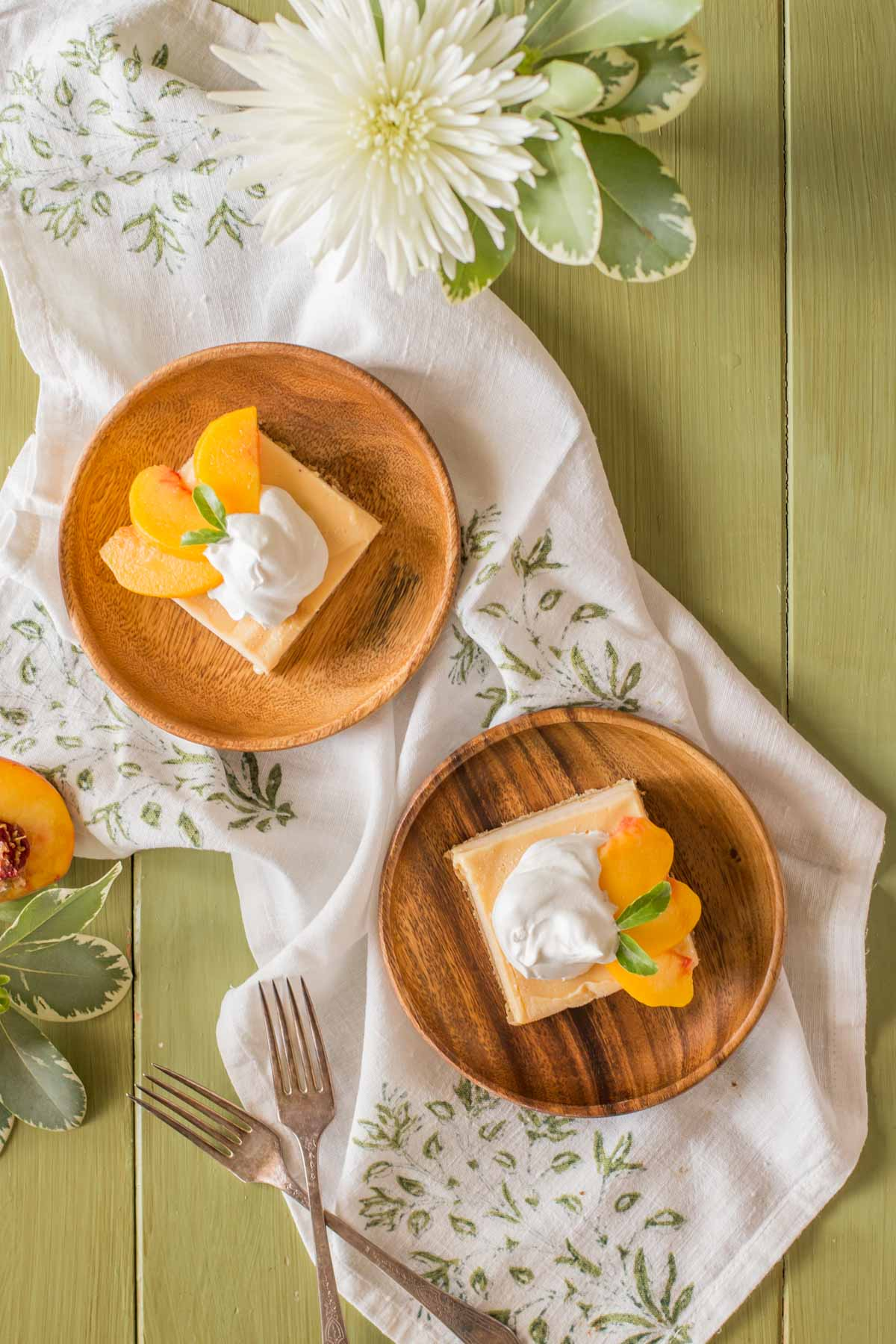 Two wood plates, each with an Easy Homemade Peach Ice Cream Bar on it, topped with whipped cream and fresh peach slices.