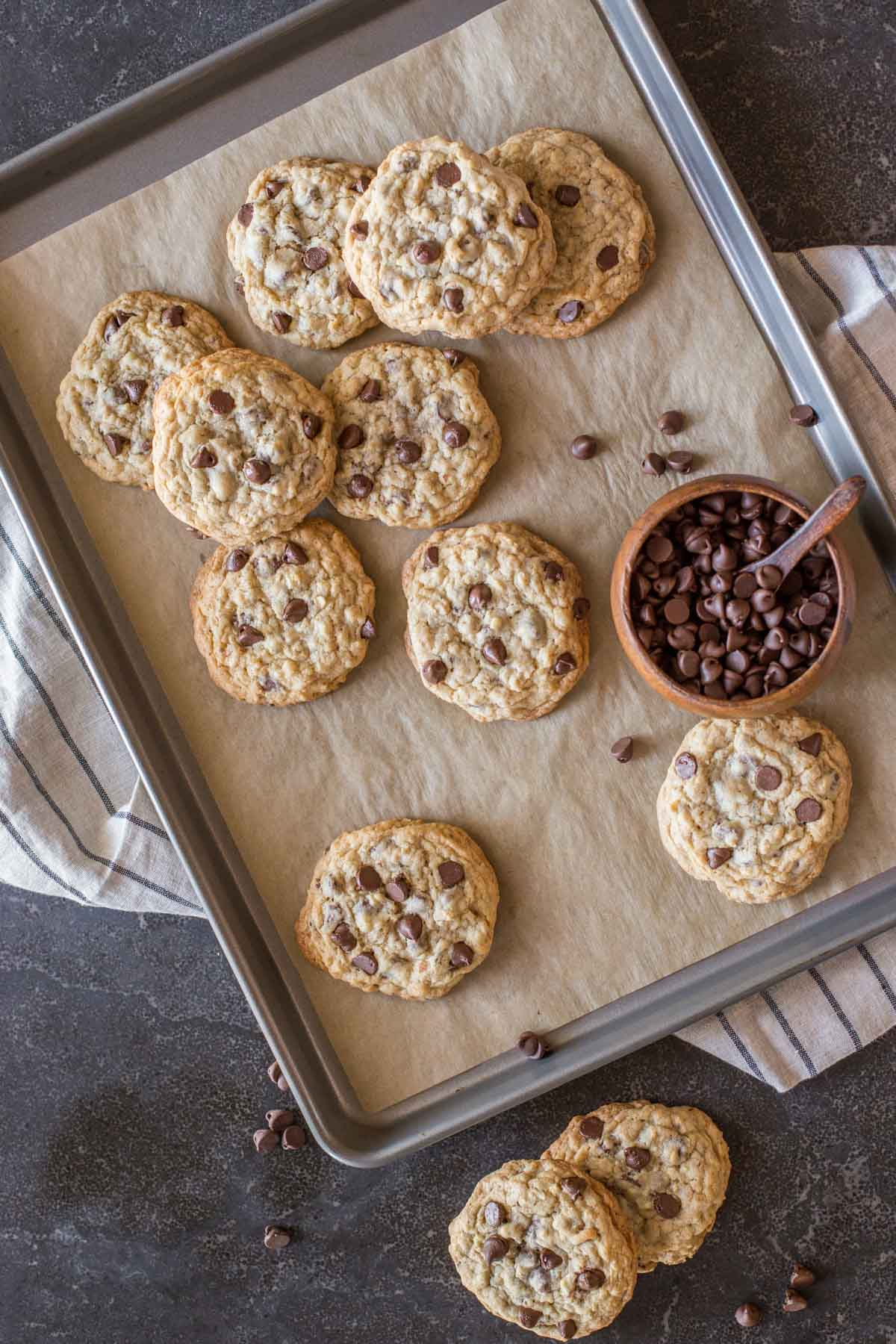 Bakery Style Oatmeal Chocolate Chip Cookies on a parchment paper lined baking sheet, along with a small wood bowl of chocolate chips, and two cookies sitting next to the baking sheet.