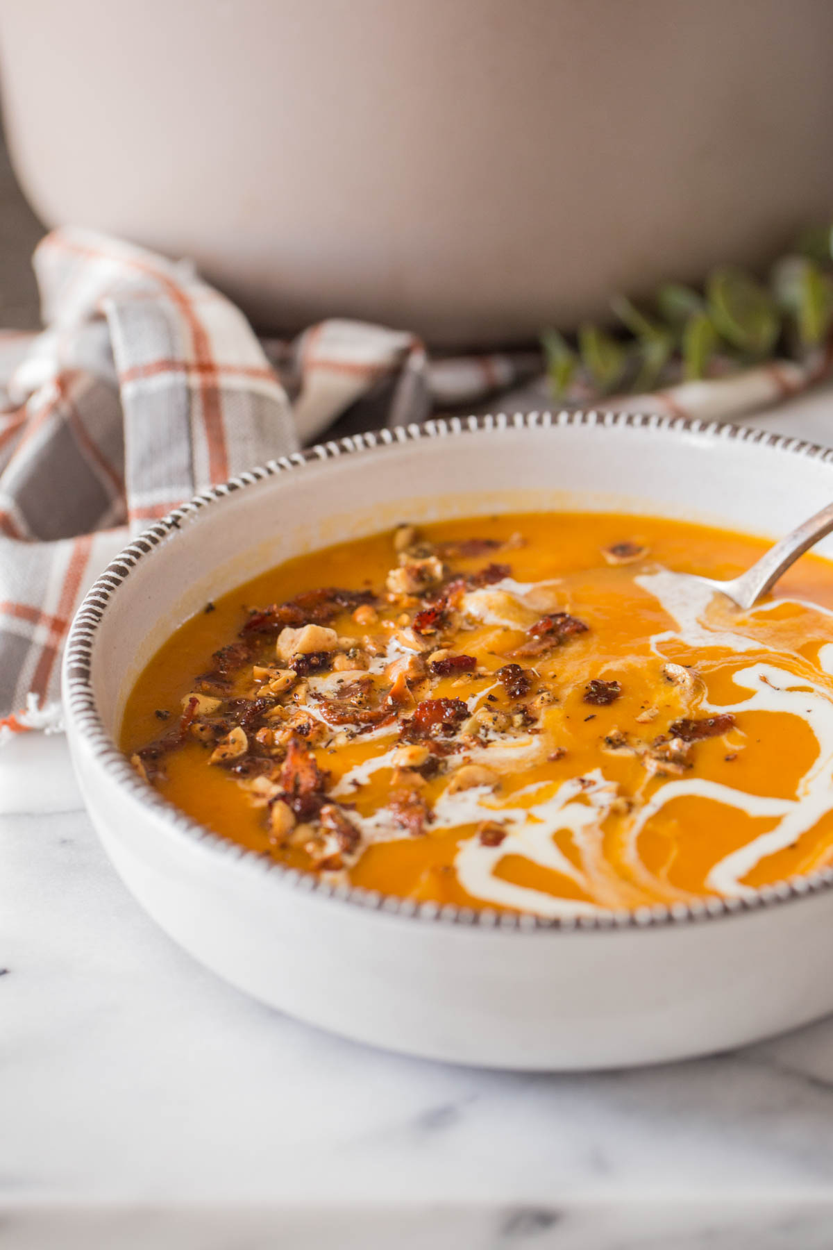 Roasted Butternut Squash Soup in a bowl with a swirl of heavy cream, and topped with a sprinkle of bacon and hazelnuts.