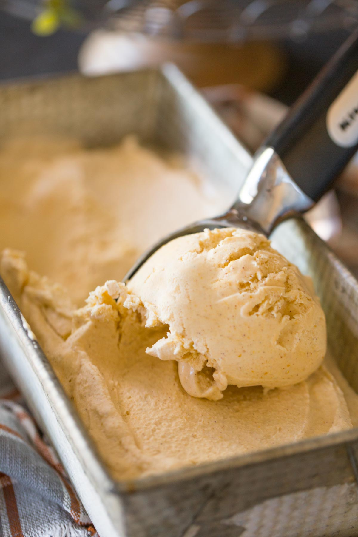 Homemade Pumpkin Pie Ice Cream being scooped from a loaf pan container.