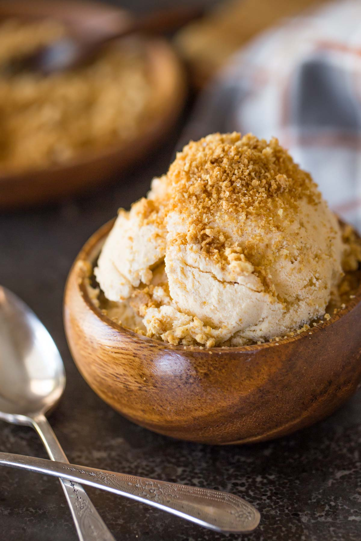 Homemade Pumpkin Pie Ice Cream in a wood bowl, topped with crushed graham cracker crumbs.