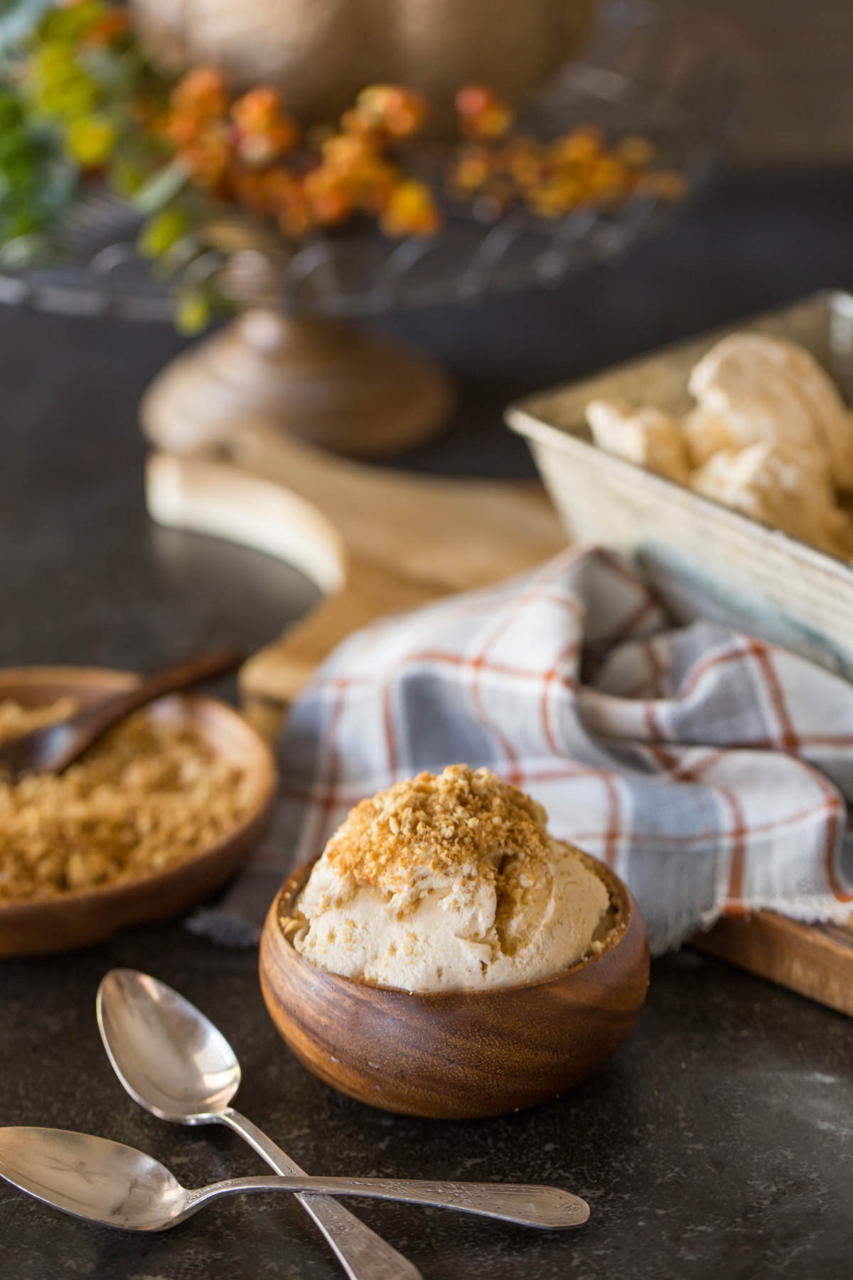 A wood bowl of Homemade Pumpkin Pie Ice Cream topped with crushed graham cracker crumbs, with two spoons sitting next to it, and a wood plate of crushed graham cracker crumbs in the background, along with the loaf pan container of Homemade Pumpkin Pie Ice Cream.