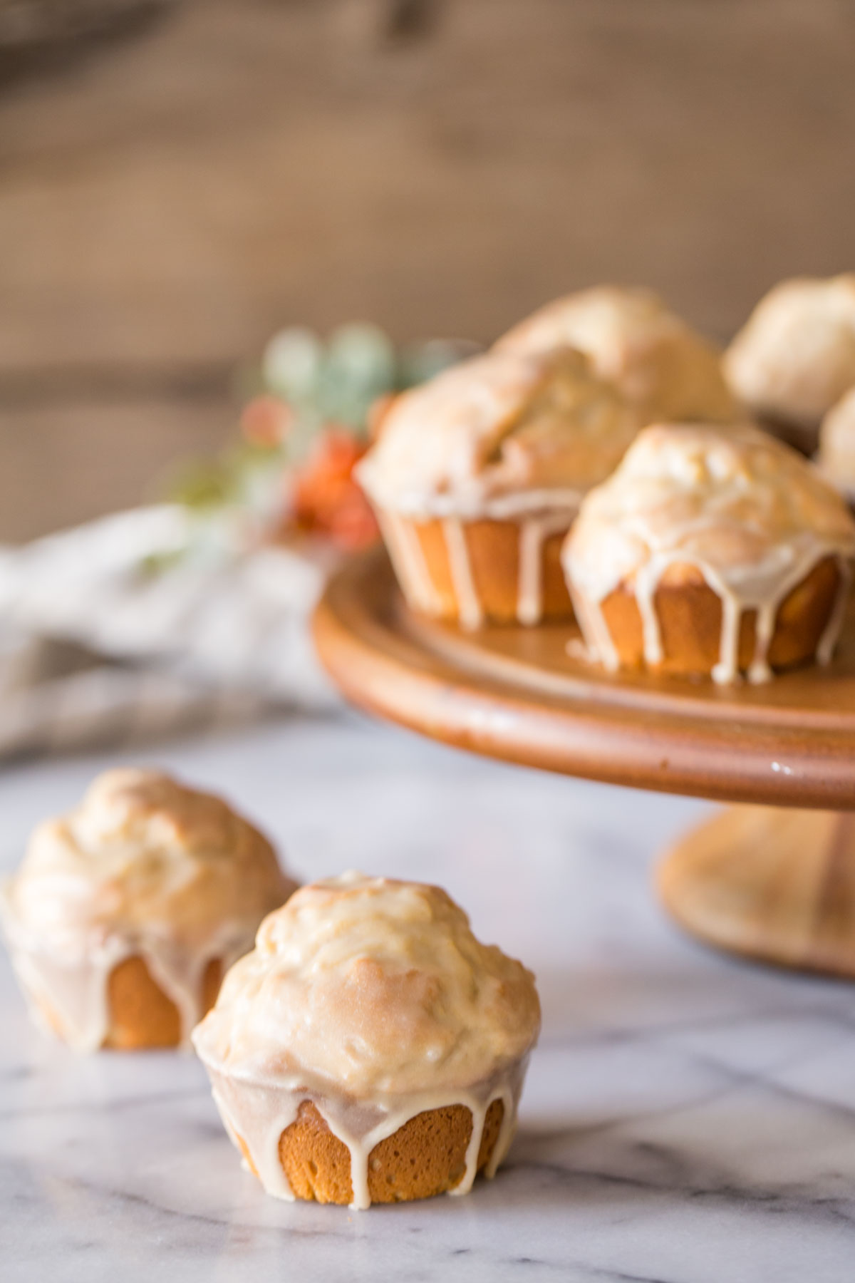 Two Maple Glazed Donut Muffins sitting next to a wood cake stand with more Maple Glazed Donut Muffins on it.