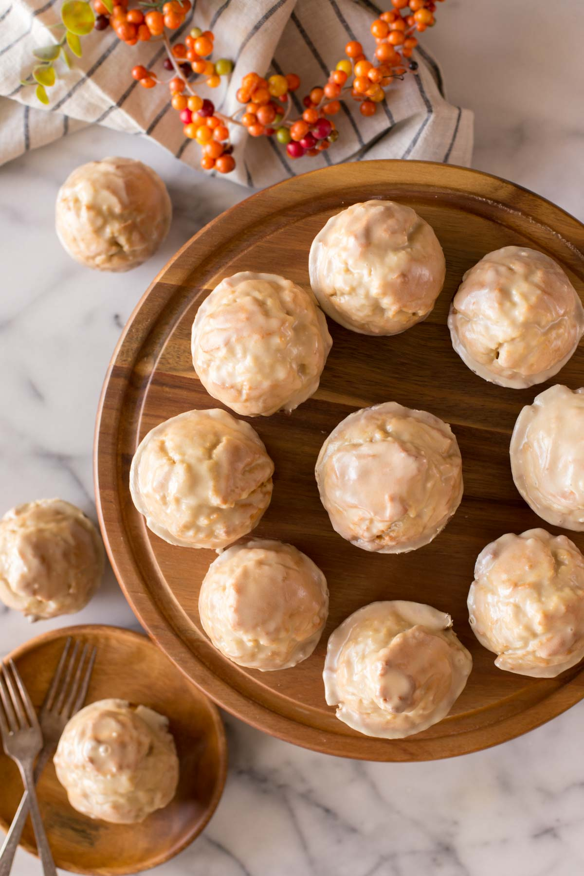 Maple Glazed Donut Muffins on a wood cake stand, with three Maple Glazed Donut Muffins sitting next to the cake stand, one of them on a wood plate with two forks.