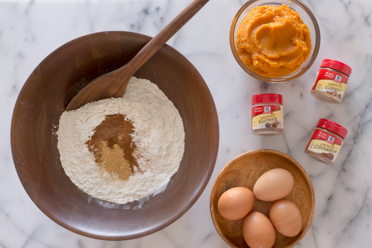 A large wood bowl of the dry ingredients for the Pumpkin Spice Coffee Cake, sitting next to a glass bowl of pumpkin puree, three McCormick spice containers, and a wood plate with four eggs on it.