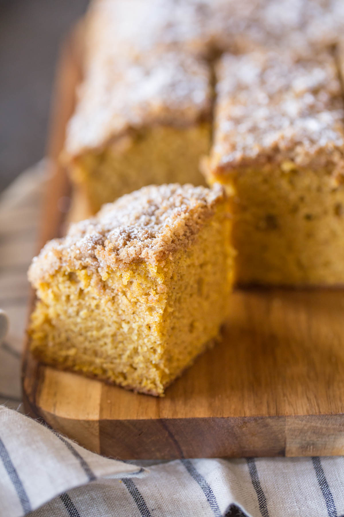 Pumpkin Spice Coffee Cake sliced into square servings on a cutting board.