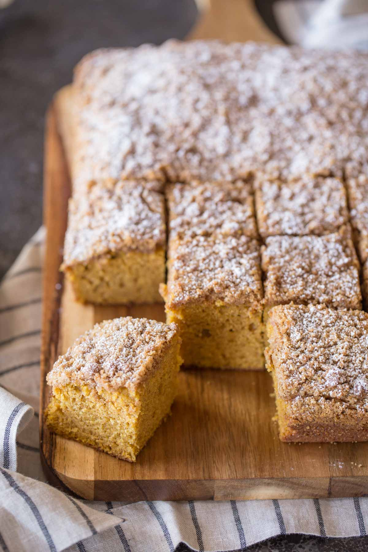 Pumpkin Spice Coffee Cake cut into square servings on a cutting board.
