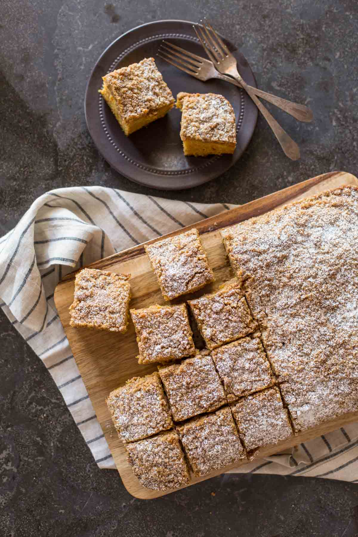 Pumpkin Spice Coffee Cake on a cutting board, with half of the cake cut into square servings, and a plate with two pieces of the cake and two forks sitting next to the cutting board.
