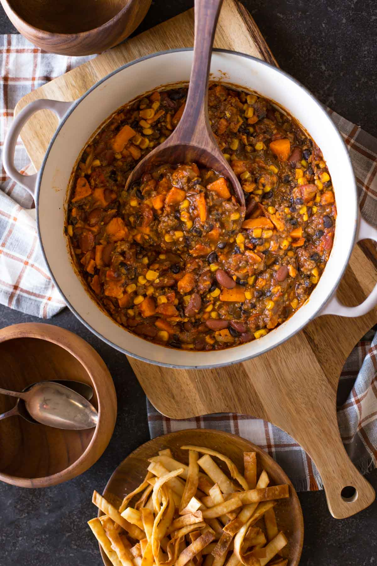 A large pot of Sweet Potato Chili with a wooden spoon in it, and a plate of Fried Tortilla Strips and wood bowls next to the pot.