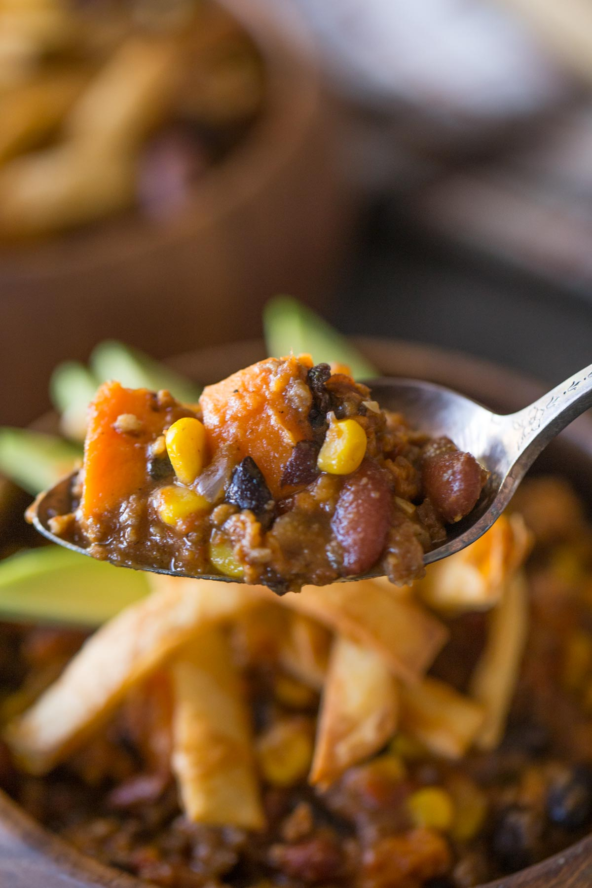 A spoon full of Sweet Potato Chili, with a wood bowl of Sweet Potato Chili, topped with Fried Tortilla Strips and sliced avocado in the background.