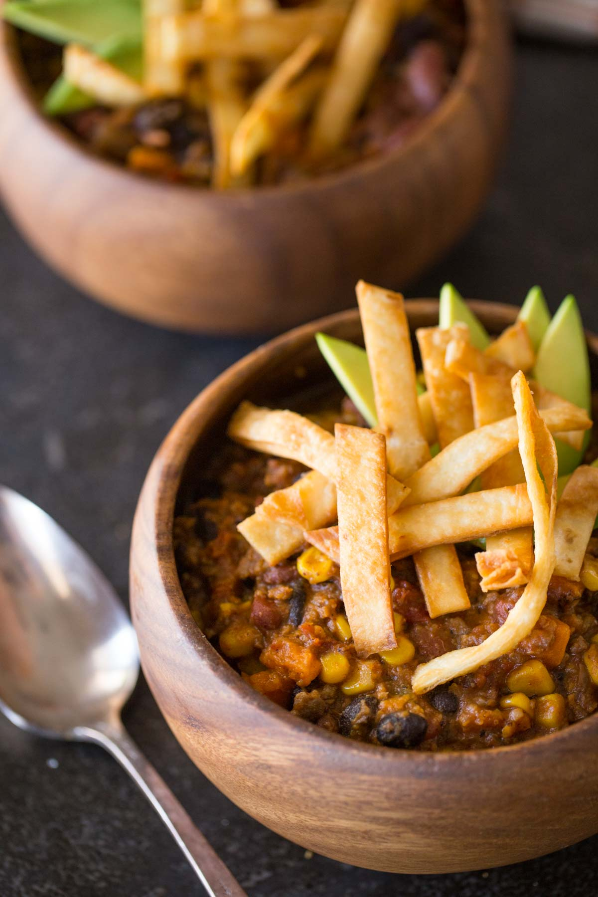 Two wood bowls of Sweet Potato Chili, topped with Fried Tortilla Strips and sliced avocado.