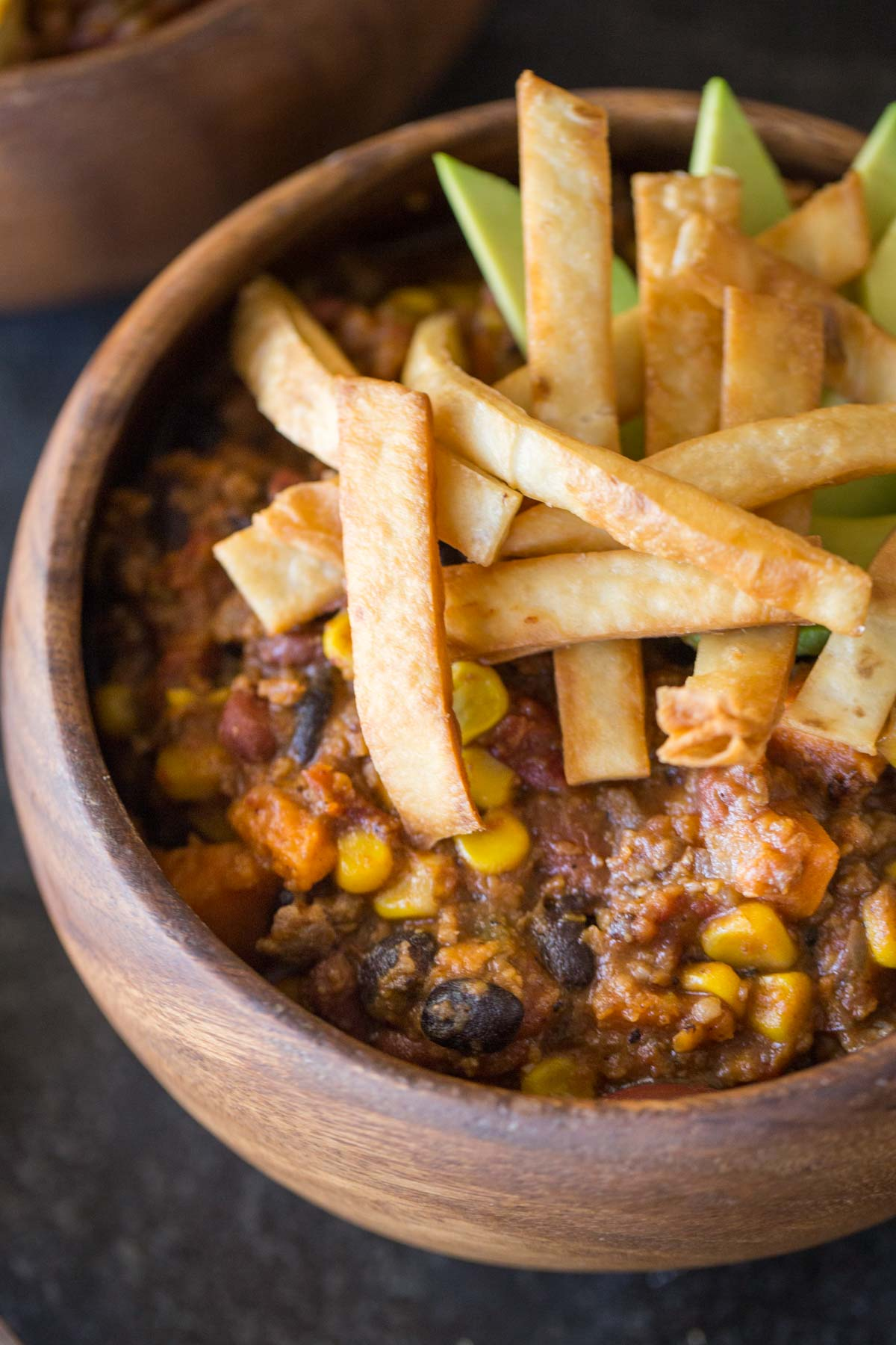 A wood bowl of Sweet Potato Chili, topped with Fried Tortilla Strips and sliced avocado.