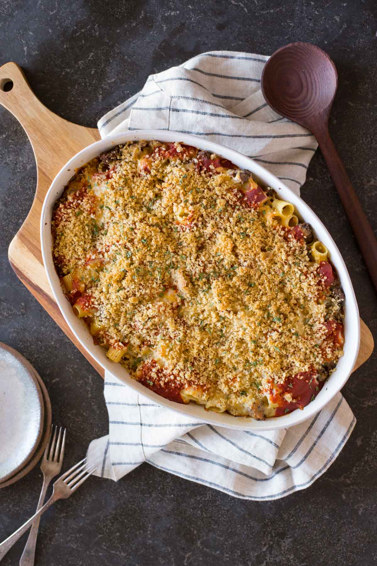 Cheesy Tomato Alfredo Pasta Bake in a baking dish, with a serving spoon, plates and forks beside it.
