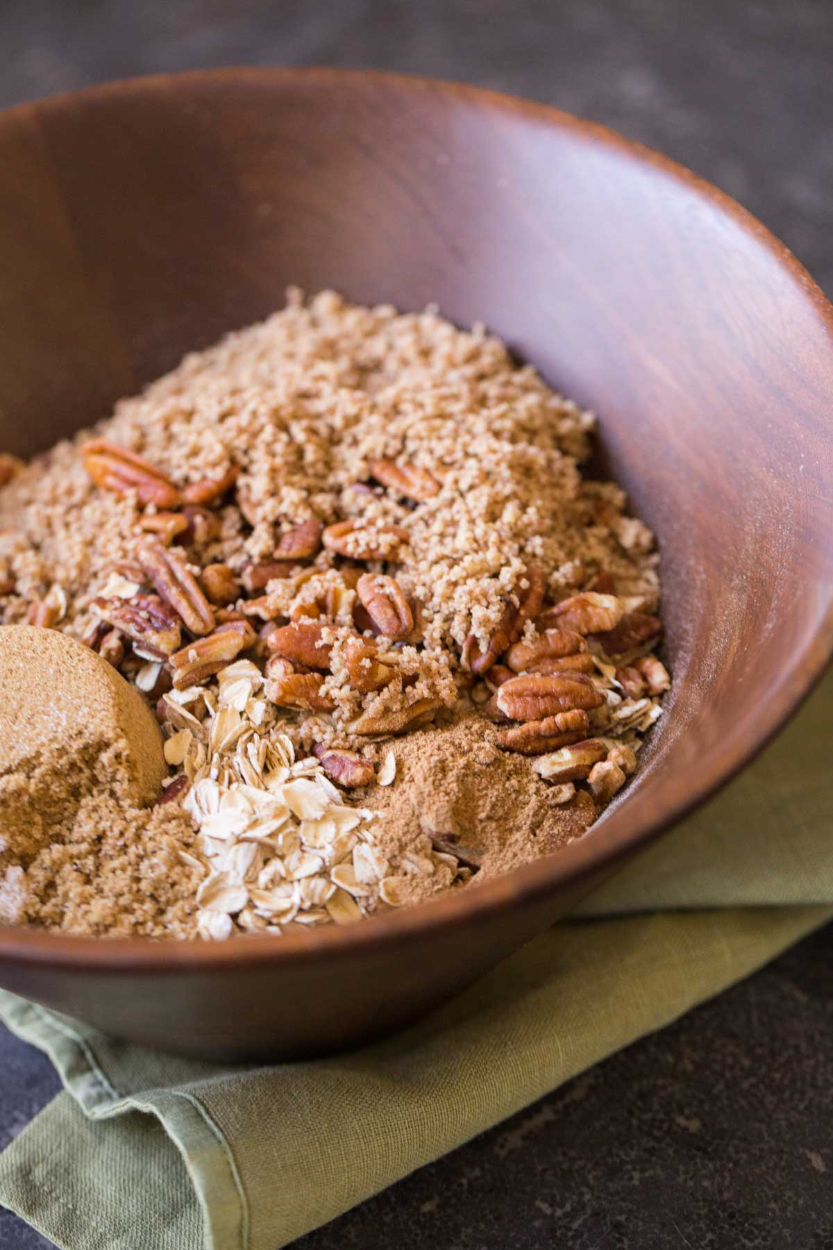 Ingredients for the Gingerbread Spice Granola in a large wood mixing bowl.