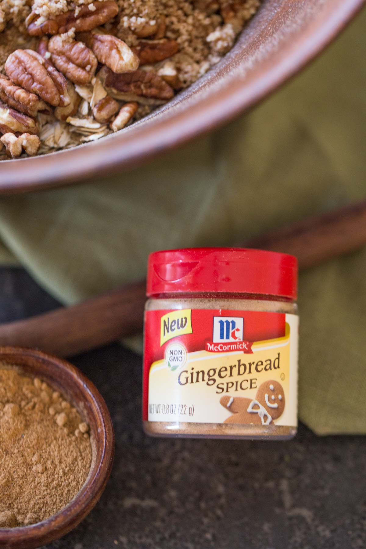 A container of McCormick Gingerbread Spice mix, sitting next to a small wood bowl of the spice mix and a large bowl of the Gingerbread Spice Granola ingredients.