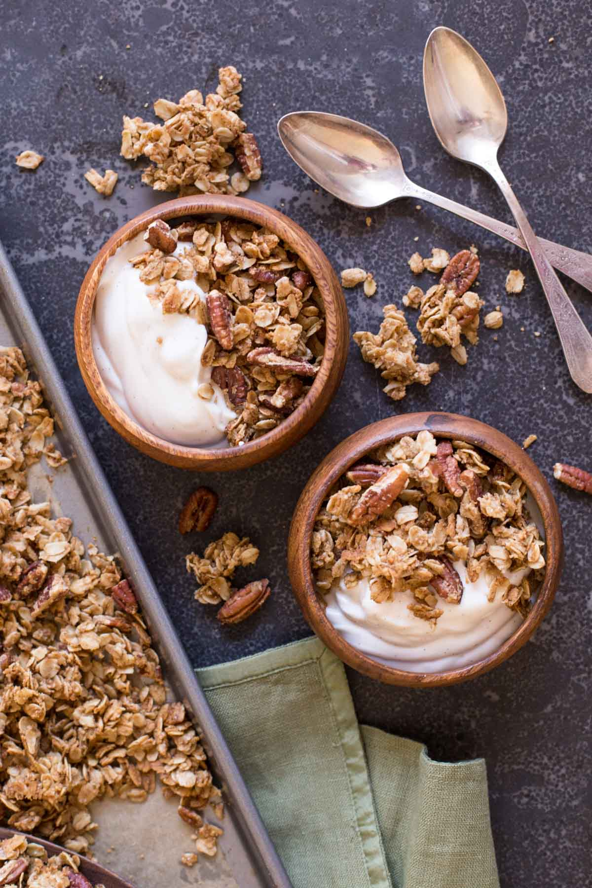 Two bowls of yogurt and Gingerbread Spice Granola, with two spoons next to them.