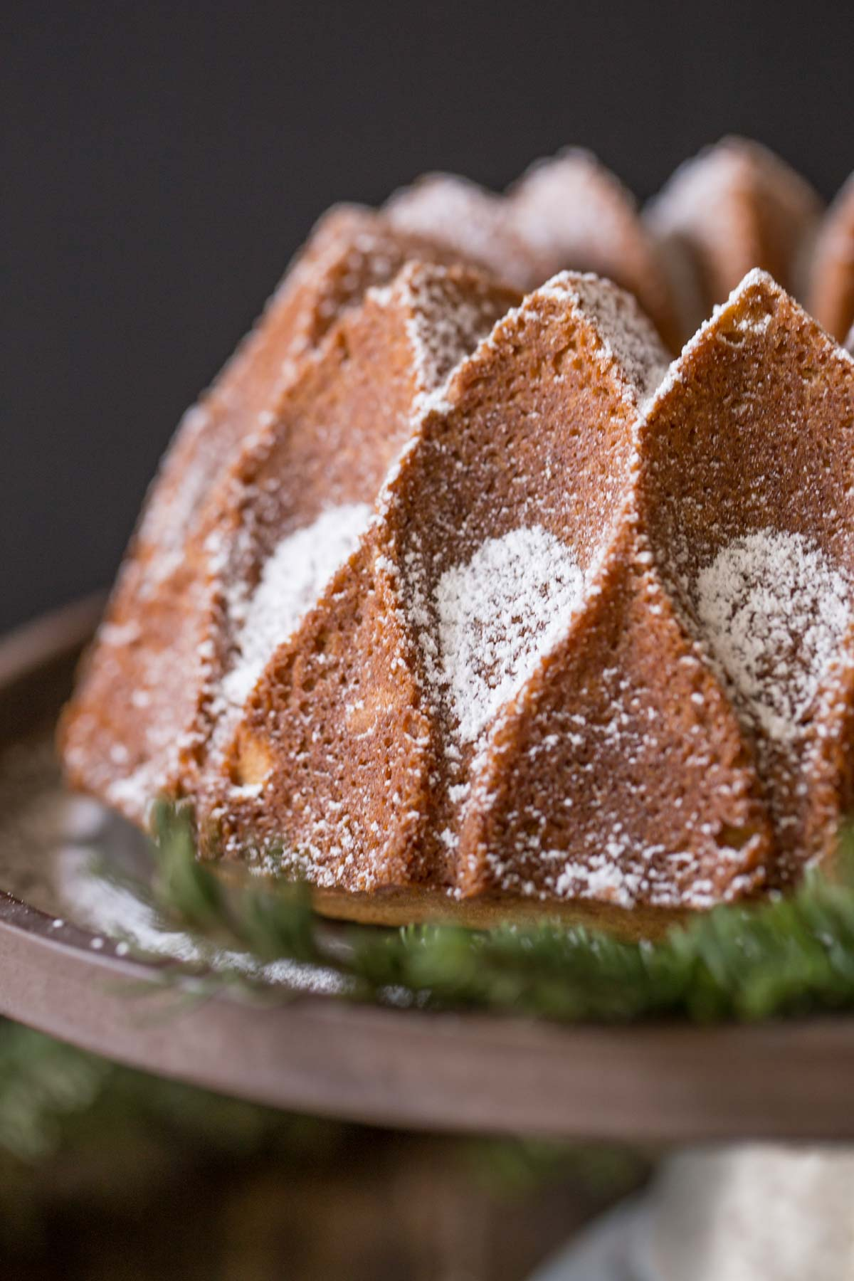 Gingerbread Bundt Cake on a cake stand, dusted with powdered sugar.