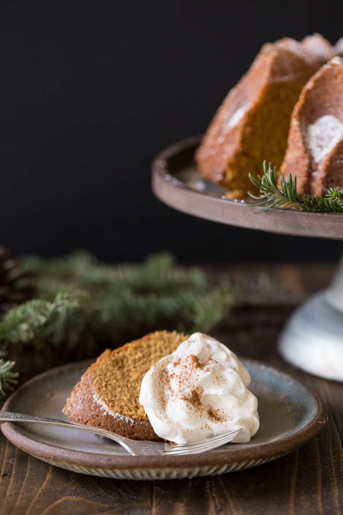 A slice of Gingerbread Bundt Cake on a plate, topped with whipped cream, sitting next to the rest of the Gingerbread Bundt Cake on a cake stand.