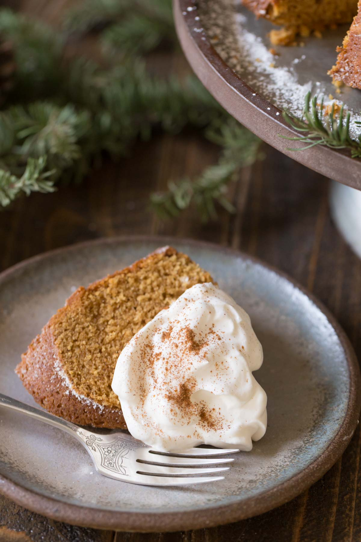 A slice of Gingerbread Bundt Cake topped with whipped cream, on a plate with a fork.