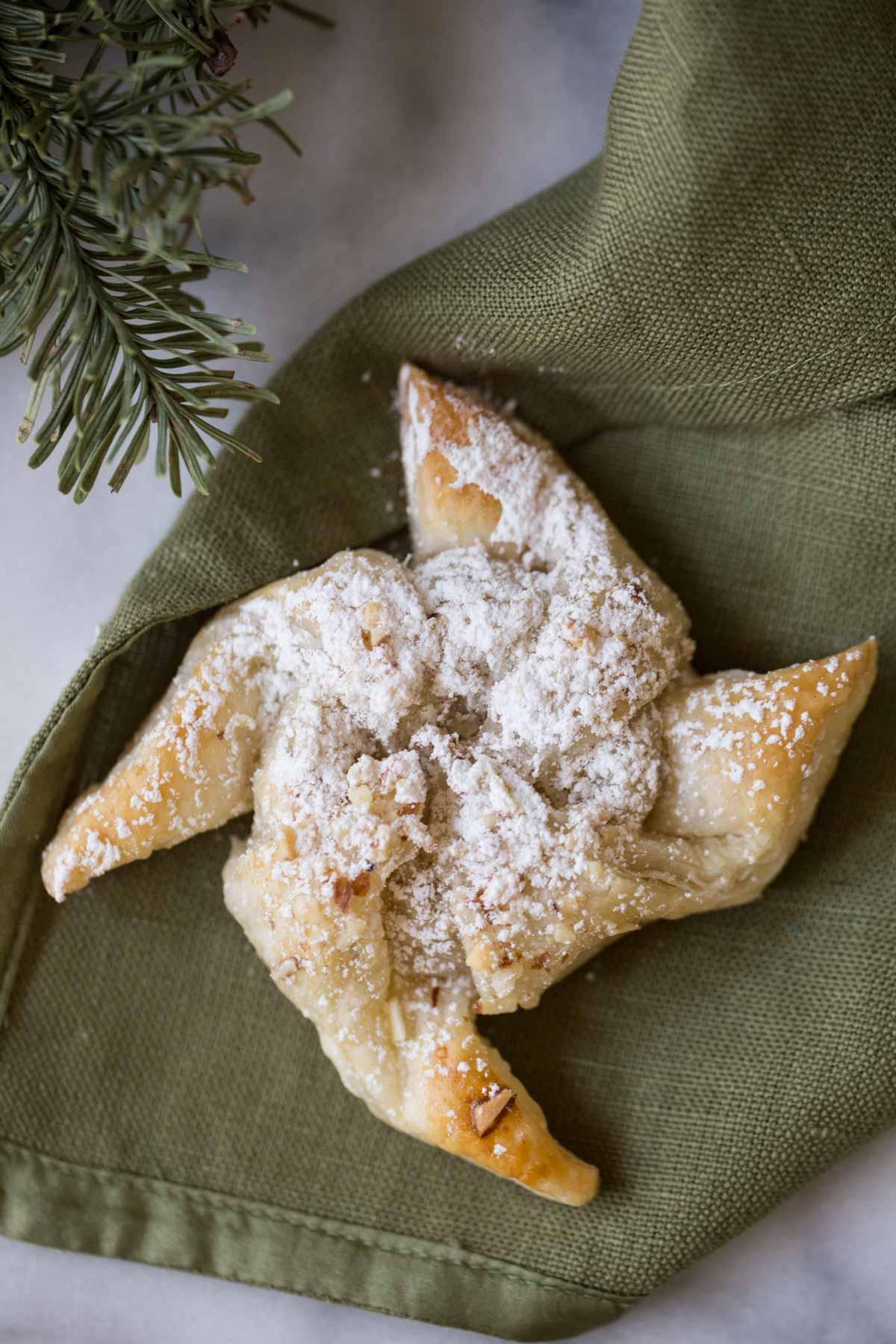 A Make Ahead Almond Pinwheel sitting on a green cloth napkin.