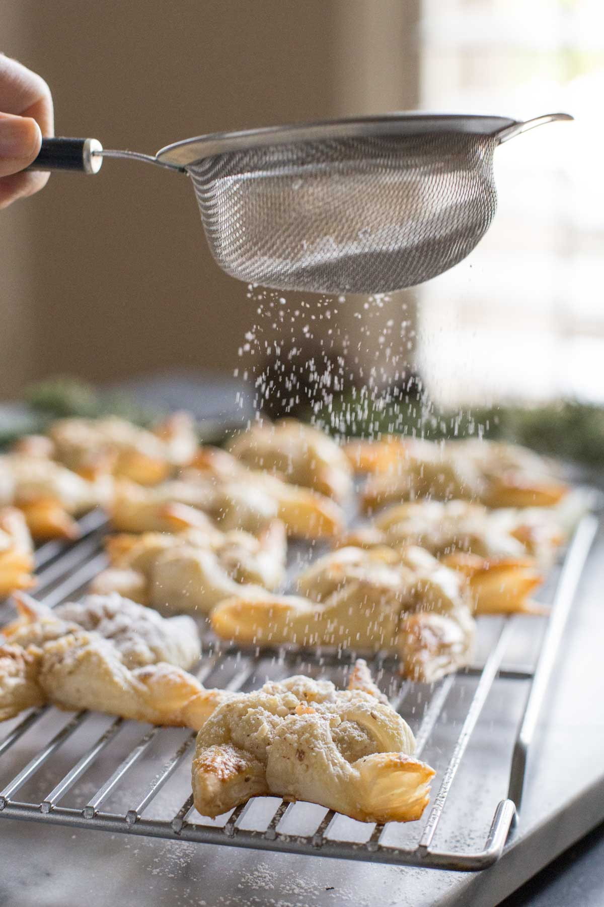 Make Ahead Almond Pinwheels on a cooling rack, being sprinkled with powdered sugar.