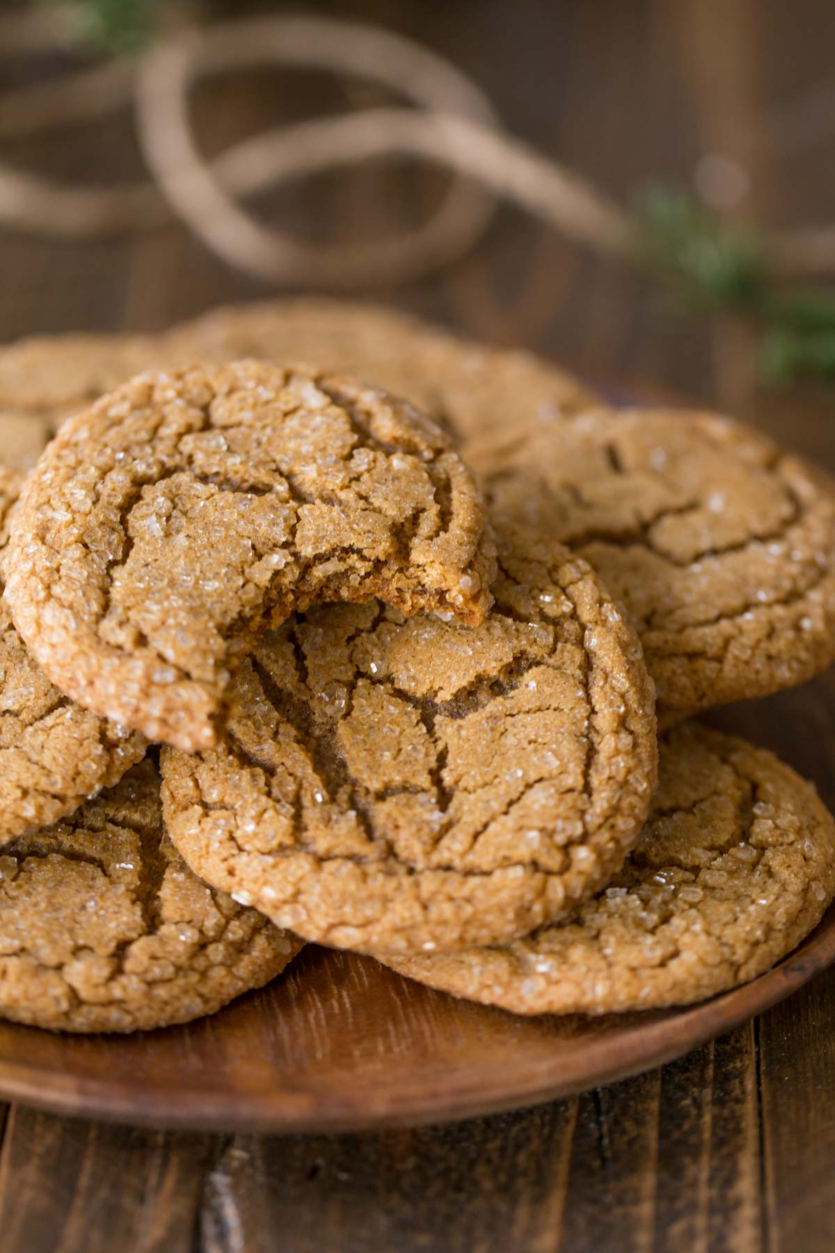 A wood plate full of Old Fashioned Ginger Snaps, with a bite taken out of the one on top.