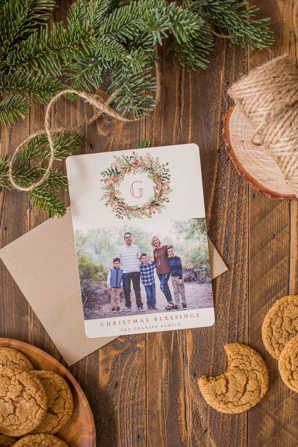 A Christmas Card that is sitting next to a plate of Old Fashioned Ginger Snaps, and some more Old Fashioned Ginger Snaps on the other side of the card, with a bite taken out of one of them.